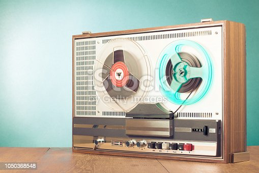 istock Retro reel to reel audio tape recorder on table in front turquoise background. Old instagram style filtered photo 1050368548
