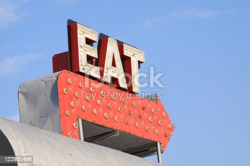 Retro sign from an old diner is photographed against a blue sky.