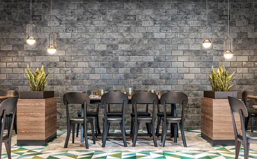Retro restaurant with tables on a distance due to covid-19 epidemic with drinks, decoration, lighting equipment, potted plants (sanseveria trifasciata) in large hardwood block pots on dark gray marble effect brick walls background. Multicolored tiled floor with a beige carpet under the tables. A vintage effect on a 3D rendered image.