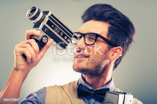 Portrait of a young man with a nerdy using old fashion camera.