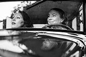 Two women in a vintage car - 1930 style. Desaturated and toned image.