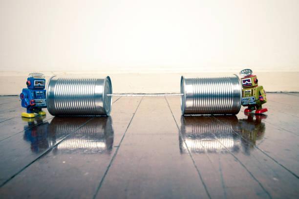 retro-roboter auf blechdose handys auf einem holzfußboden - converse taylor stock-fotos und bilder