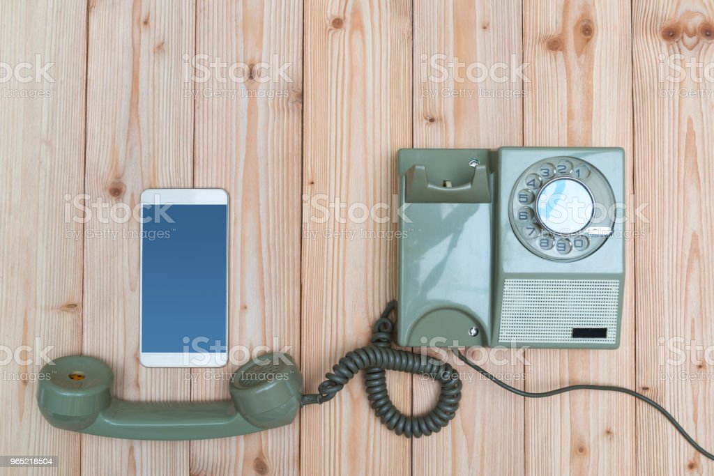 Retro rotary telephone or vintage phone with cable and new cell phone or smart phone on wood table, top view with copy space, technology progress concept. royalty-free stock photo