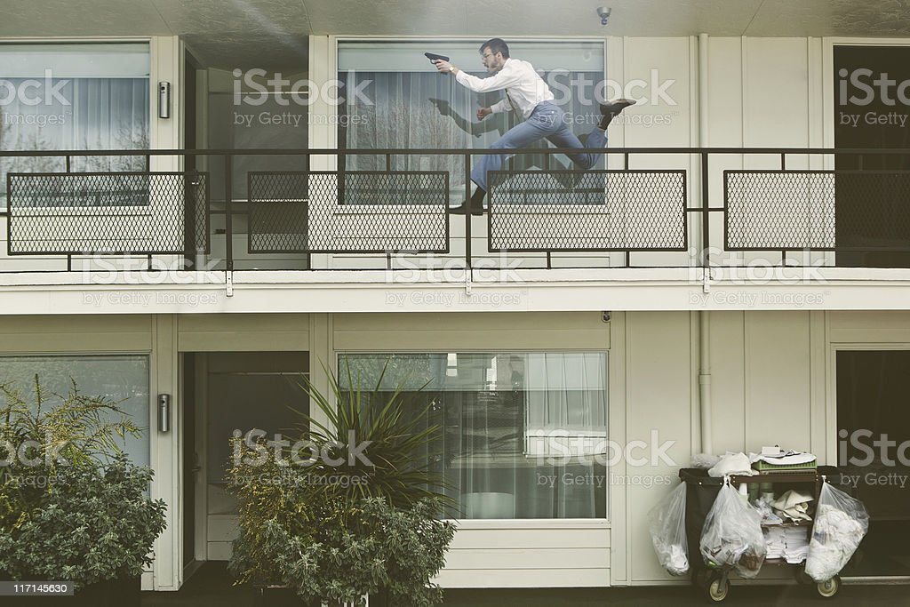 Retro Secret Agent Running With Pistol in Hotel royalty-free stock photo