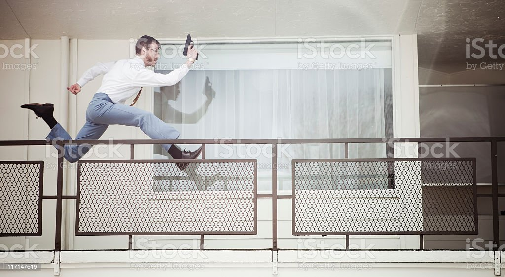 Retro Secret Agent Running With Pistol in Hotel stock photo