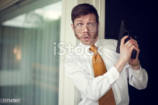 A spy or undercover agent with sideburns, mustache, and vintage 1970's / 80's style clothes peers out of a hotel room doorway into an outdoor corridor hallway, gun in hand and a funny look on his face.  Horizontal with copy space.