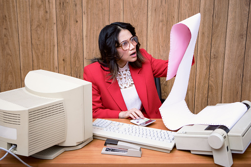 A vintage Filipino business woman at the office works at an old computer at her desk.  1980's - 1990's fashion style.  Wood paneling on wall in the background.
