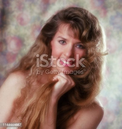 A color self-portrait from the 1980s of a 30-something year old woman with long wavy blond hair smiling into camera.