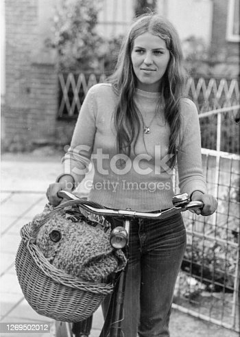 Black and whit retro picture of a young woman with here old bicycle back in the seventies