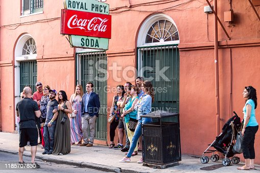 New Orleans, USA - April 23, 2018: Retro sign for coca-cola soda and royal pharmacy on street in Louisiana town and many people