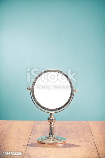 istock Retro silver makeup mirror frame on aged oak wooden table front mint blue wall background. Vintage style filtered photo 1066708068