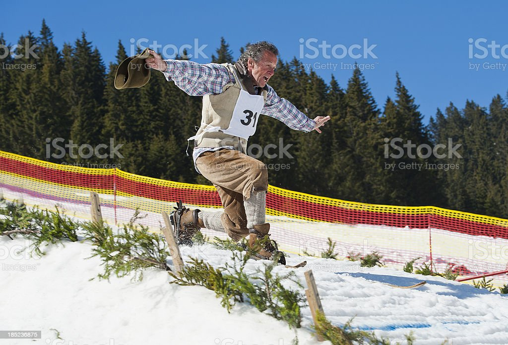 Retro ski jumper landing in telemark style stock photo