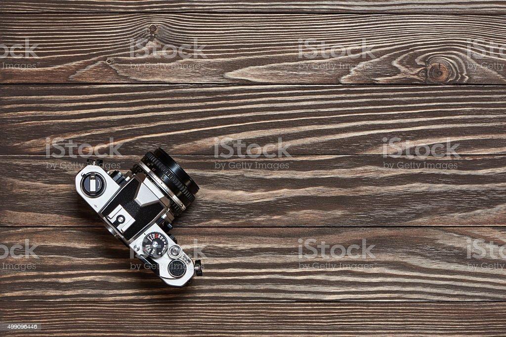Retro SLR camera on old wooden background stock photo