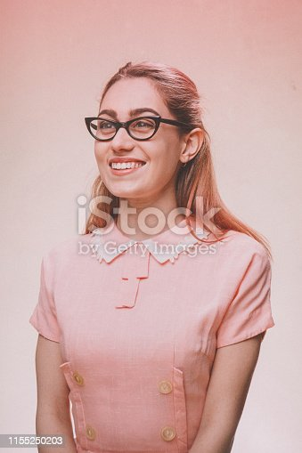 A 1950's styled young woman in a vintage pink dress and cats eye glasses.  Pink background.
