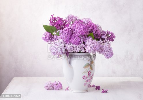 Retro still life with a bouquet of Lilac on a white wooden table.  Soft focus.