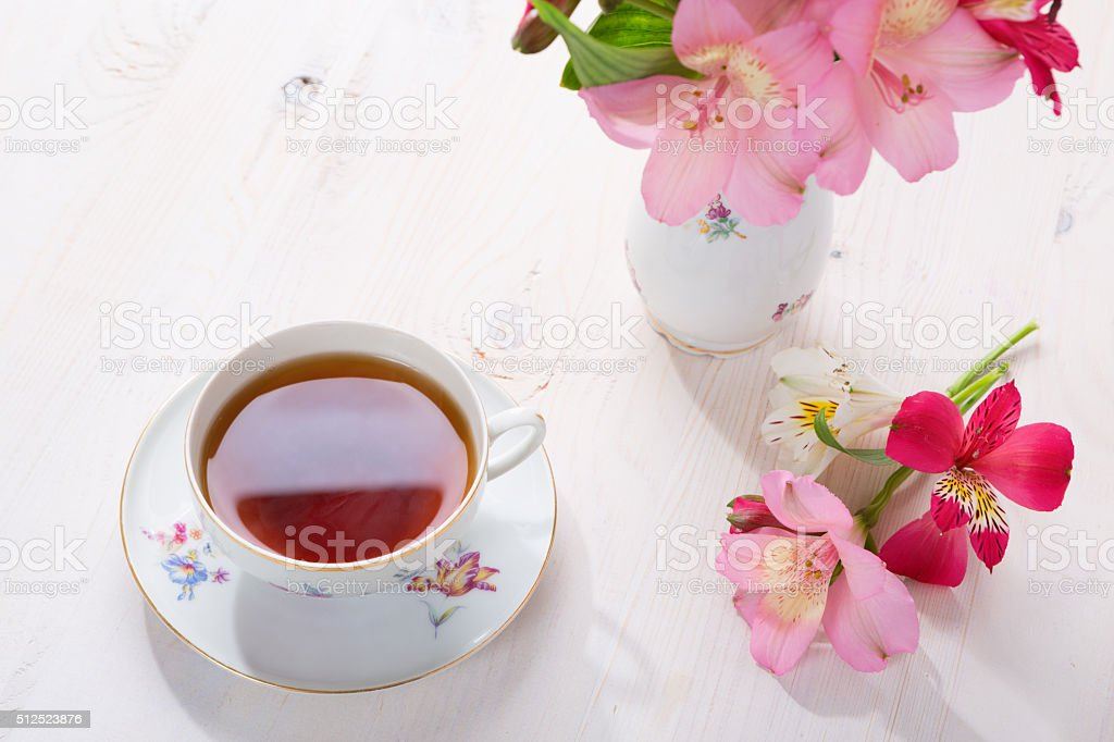 Retro still life with cup of tea and flowers. stock photo