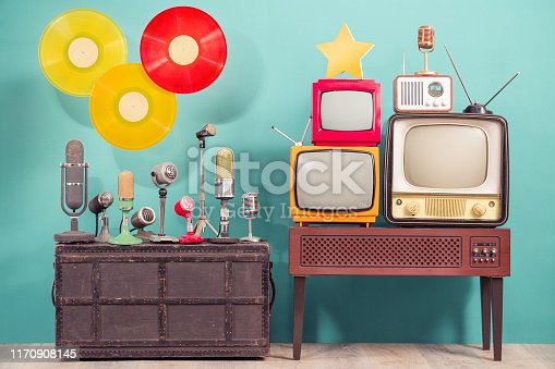 istock Retro studio microphones, outdated TV set, old FM radio, golden award star,  flying multicolor LP vinyl record discs front blue background. Nostalgia music and journalism concept. Vintage style photo 1170908145