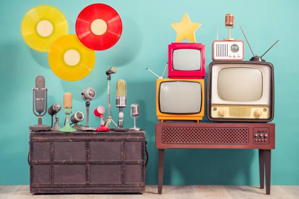 Retro-Studio-Mikrofone, veraltete TV-Gerät, alte FM-Radio, goldene Auszeichnung Stern, fliegende multicolor LP Vinyl Schallplatten Scheiben vordem blauen Hintergrund. Nostalgie-Musik und Journalismus-Konzept. Vintage-Stil Foto – Foto