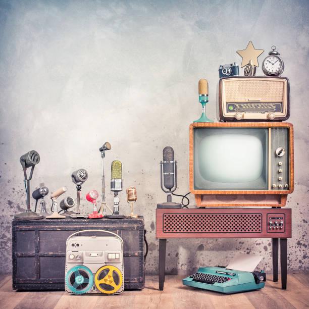 Retro-Studio-Mikrofone Set, veraltetes Fernsehen, altes Rundfunkradio, Journalistenrolle zum Rollbandgerät, gealterte Uhr, Filmkamera, goldener Award-Star, Schreibmaschine. Journalismus-Konzept. Vintage-Stil Foto – Foto