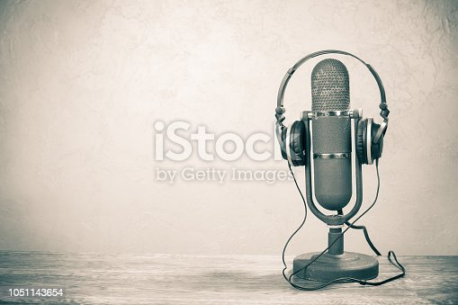 istock Retro studio ribbon microphone from 50s with headphones on table. Vintage old style sepia photo 1051143654