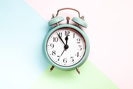 1035679160 istock photo Retro style alarm clock over the pastel background 1035679172