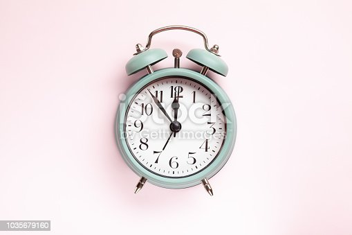 istock Retro style alarm clock over the pink background 1035679160