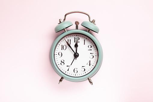 1035679160 istock photo Retro style alarm clock over the pink background 1035679160