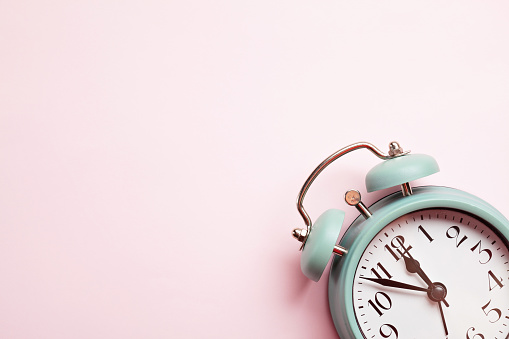 1035679160 istock photo Retro style alarm clock over the pink background 1035679170