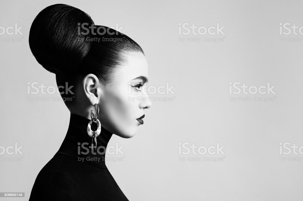 Retro style black and white fashion portrait of elegant female model with hair bun hairstyle and eyeliner makeup stock photo