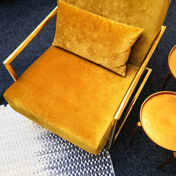 Retro style dark yellow velvet armchair and golden side table stock photo