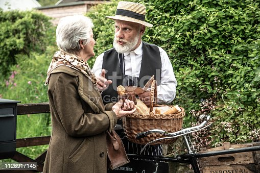 retro style deliveryman with customer - selling bread and meat - ration book/war years