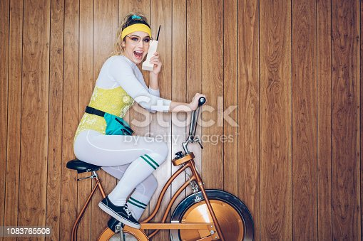 A woman wearing exercise clothing styled after the 1980's and 1990's pedals hard on a stationary fitness bike in a vintage room, complete with wood paneling on the walls. She wears a leotard and a fanny pack and talks on an early mobile phone dubbed the