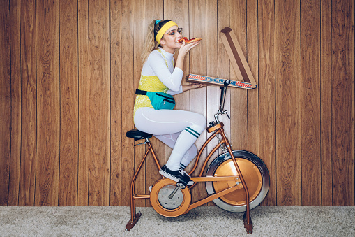 A woman wearing exercise clothing styled after the 1980's and 1990's pedals hard on a stationary fitness bike in a vintage room, complete with shag carpet and wood paneling on the walls. She wears a leotard and a fanny pack and eats from a large box of pizza.