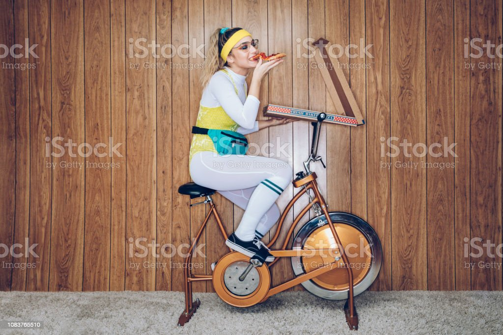 Retro Style Exercise Bike Woman Eighties Era Eating Pizza stock photo