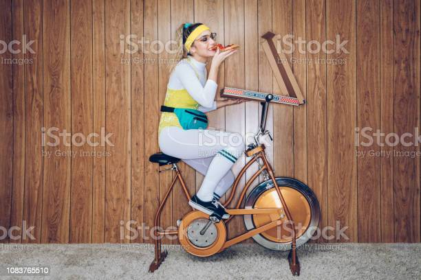 Retro Style Exercise Bike Woman Eighties Era Eating Pizza