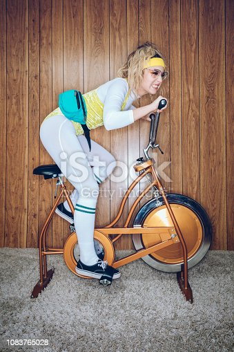 A woman wearing exercise clothing styled after the 1980's and 1990's pedals hard on a stationary fitness bike in a vintage room, complete with shag carpet and wood paneling on the walls. She wears a leotard and a fanny pack.