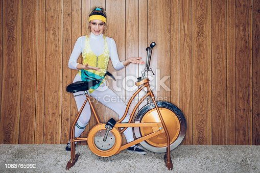 A woman wearing exercise clothing styled after the 1980's and 1990's pedals hard on a stationary fitness bike in a vintage room, complete with shag carpet and wood paneling on the walls. She wears a leotard and a fanny pack, showing off her bike.