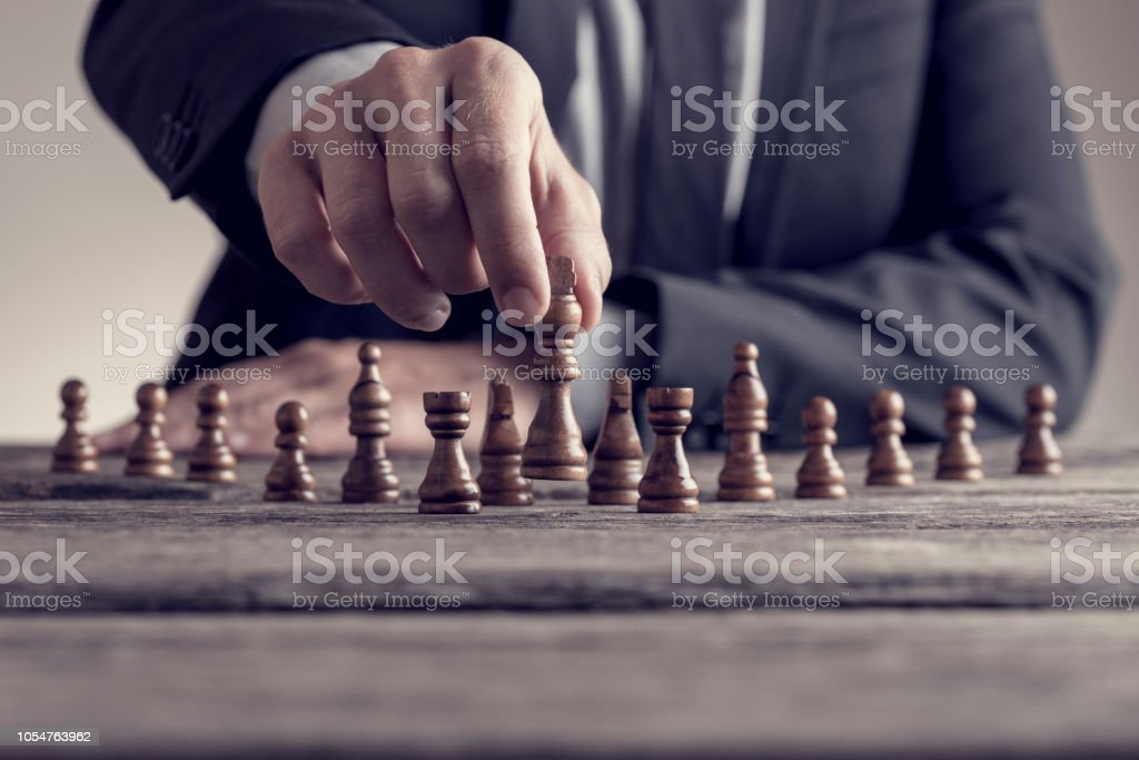 Retro style image of a businessman playing a game of chess on an old wooden table stock photo
