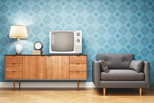 Living room decorated in retro style with TV stand, armchair and old television.