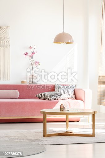 Retro style, millennial pink pendant lamp above a simple, wooden coffee table in a sunny, white living room interior with patterned pillows on a velvet sofa
