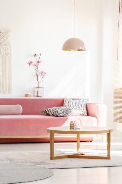 retro-stil, tausendjährigen rosa pendelleuchte über eine einfache, hölzerne couchtisch in einem sonnigen, weiße wohnzimmer interieur mit gemusterten kissen auf dem sofa samt - hellrosa zimmer stock-fotos und bilder