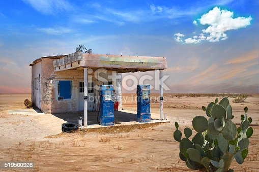 Old gas station with blue pumps in deserted arid landscape with a prickly pear cactus. Vintage look.