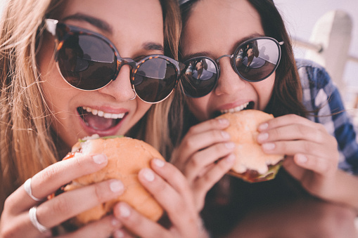 Closeup portrait of two teenage girls who are best friends, wearing hipster sunglasses about to take bites out of large burgers outdoors with a retro style develop