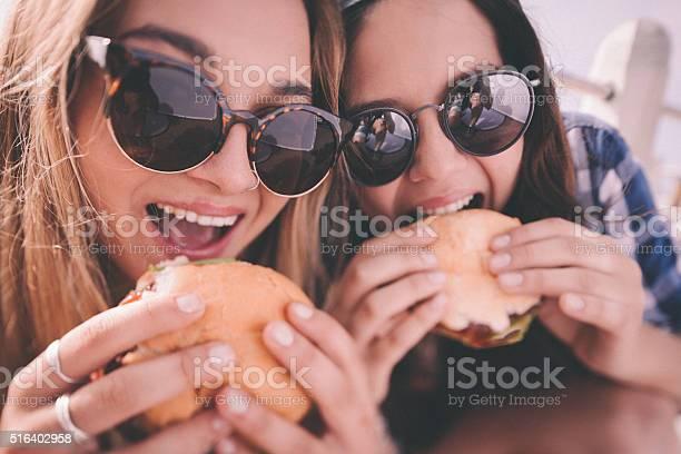 Retro style shot of teenage girl best friends eating burgers picture id516402958?b=1&k=6&m=516402958&s=612x612&h=xpxtjjvmw7yq1bpk0sanhxskp uiqce79di1vfpw9ks=