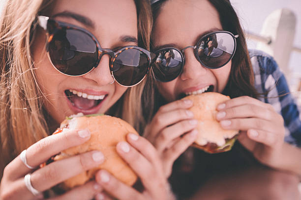 Retro style shot of teenage girl best friends eating burgers stock photo