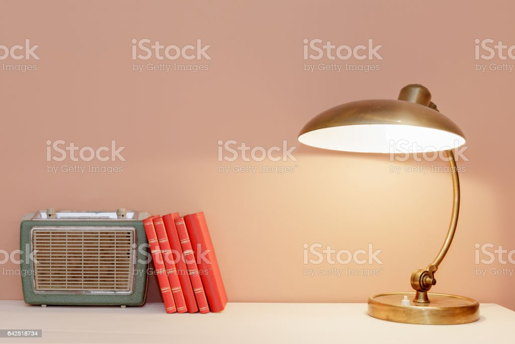 Retro Style Table With Lamp, Books and Radio stock photo