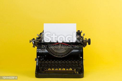 Old typewriter on a yellow background.