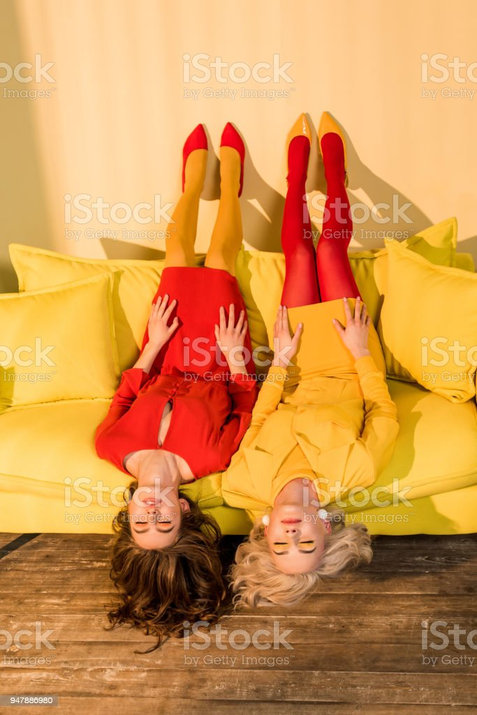 retro styled beautiful girls in colorful dresses lying upside down on...