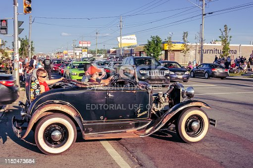 Moncton, New Brunswick, Canada - July 8, 2017 : During 2017 Atlantic Nationals Automotive Extravaganza, Ford Model A roadster takes a Saturday evening cruise on Mountain Road. A young boy wearing sun glasses sits in the rear rumble seat while people gather onto the sidewalks to watch the classic cars cruising.