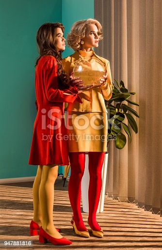 109350576 istock photo retro styled girls in colorful dresses holding aquarium with fish and looking away at home 947881816